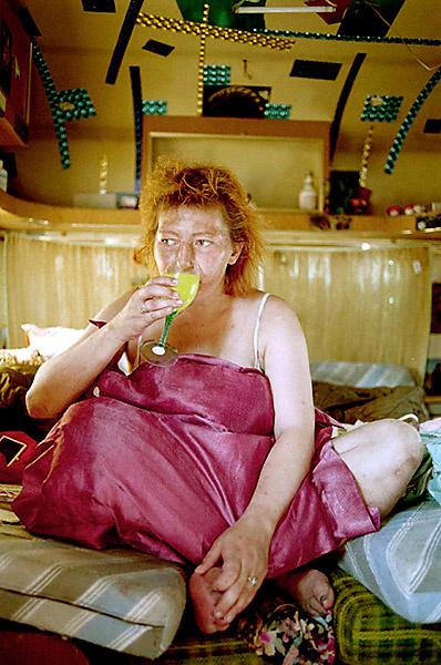Homeless - Copenhagen - Homeless woman sitting in here mobile home and drinking some lemonade.